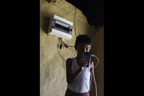 Image of a young boy half in shadow charging his phone